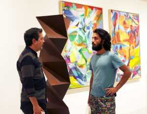 Colombian sculptor Juan Mejia, famous contemporary sculptor, miami etra fine art gallery sculpture for sale, canvas colorful art for sale, blue shirt, beard men talking