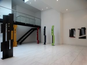 Plecto Galeria in Medellin, Sculptures by Juan Mejia, red black, green large sculptures, gallery balcony, lights, miami etra fine art gallery famous sculptor, modern artist for sale